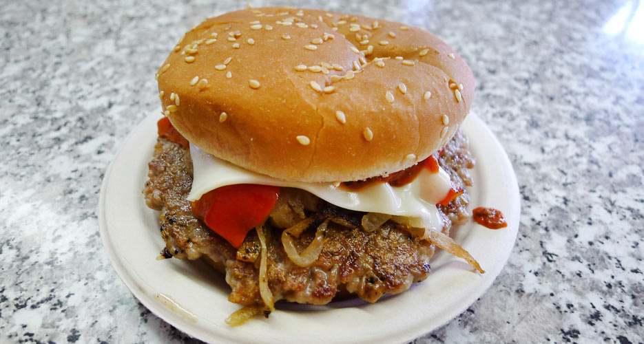 The Italian sausage sandwich at Mike's looks like a burger with white American cheese, fried onions, and ketchup.