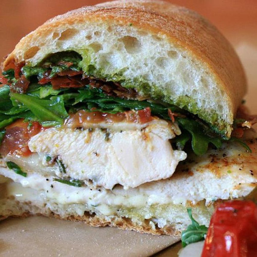 Rosemary chicken panino with crispy prosciutto, oven-cured tomato, provolone, arugula pesto, amen. (Photo: