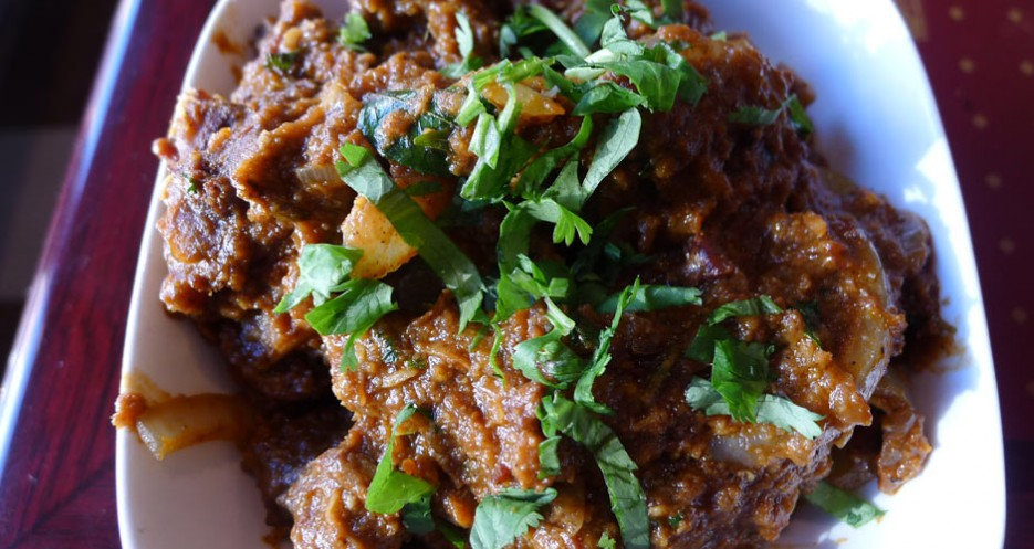 Mutton kozhambu at Chennai Flavors is a rich, dark curry featuring toasted spices.