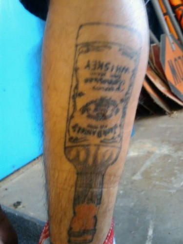 If you're gonna get a tattoo of a whiskey bottle, you should probably spring for some shading. (Photo: Twitgoo)