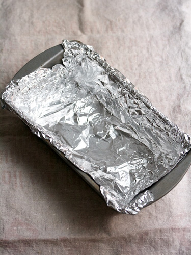 6. Get ready to assemble this cake. Take a loaf pan and line it with some foil.