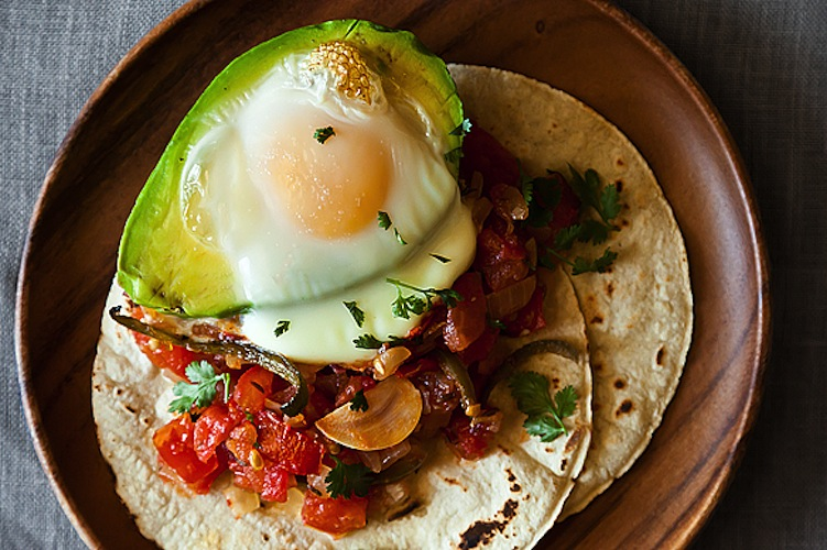 Avocado Y Huevos Caliente. It's more than a mere coincidence that when you remove the pit of an avocado, the cavity is the perfect size for an egg—it's destiny. Avocados and eggs are meant to be together and when you add spicy peppers, salsa, and warm corn tortillas, it's almost too good to be true.