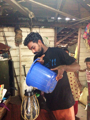 He pours the rest of the toddy in a vessel to further ferment.