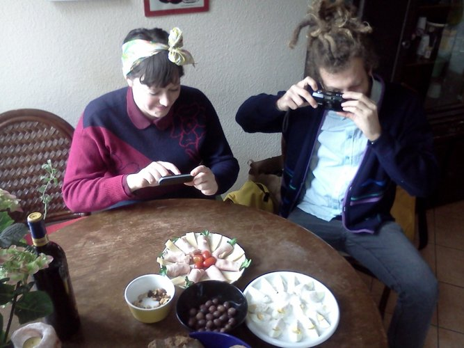 Dreads, front tied bandanas, sandwich meats, olives, and chopped hard boiled eggs. Classic picture of hipsters taking pictures of food.