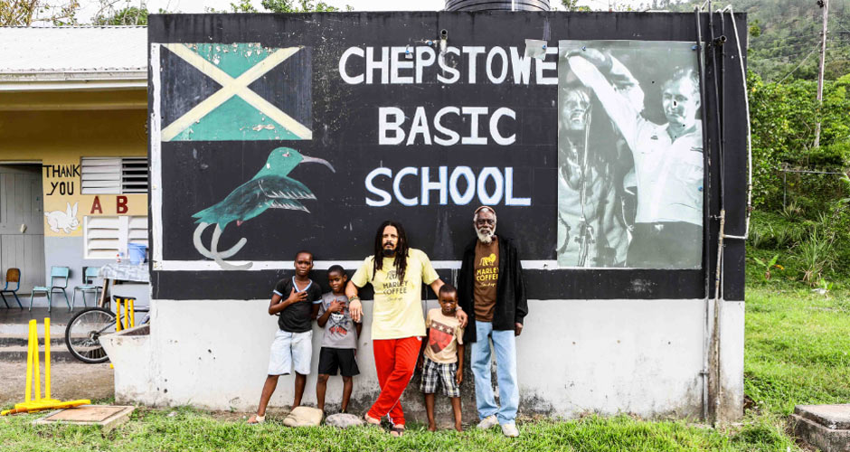 Rohan Marley with a Marley Coffee farmer and two kids from the Chepstowe community