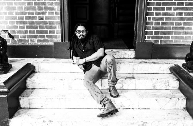 Rohan Marley sitting on the steps of his father's home, which is now the Bob Marley Museum