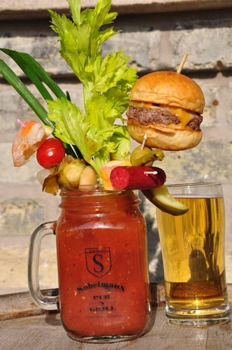 The Bloody Masterpiece at Sobelman's in Milwaukee. This bloody mary features 13 garnishes: brussel sprouts, celery, onions, mushrooms, cherry tomatoes, lemons, pickles, shrimp, sausage, cheese, olives, green onion, asparagus and a bacon cheeseburger slider. It's served with a beer back you you can wash down all the shit you've just ingested. (Photo: