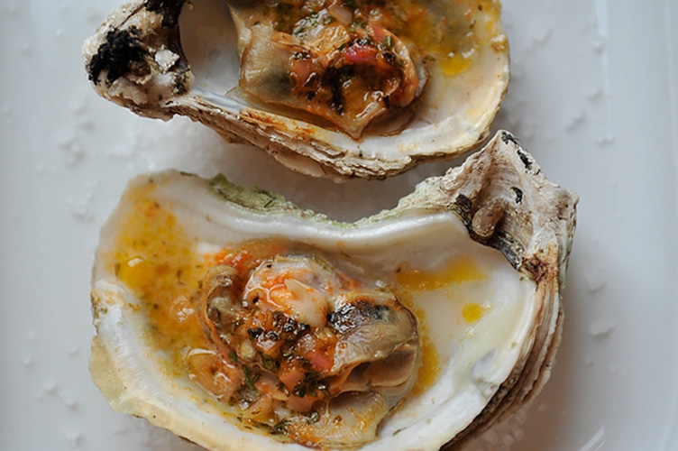 Grilled Oysters with a Sriracha Lime Butter. It's time to graduate from the ubiquitous shrimp cocktail. These grilled oysters are topped with a tangy compound butter that plumps the oysters as they grill, preventing them from drying out under direct heat.