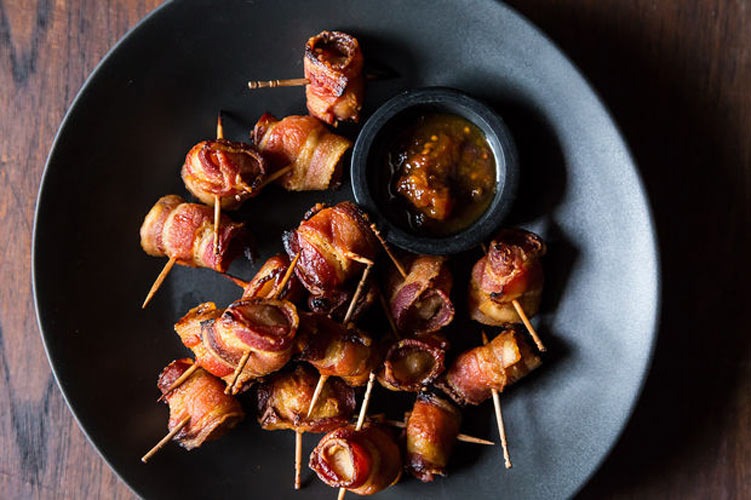 The Elegant Hors d'Oeuvre's Bacon-Wrapped Water Chestnuts. Brown sugar, mustard, water chestnuts, and bacon are all you need to make these sweet, smoky bites. Skewer them up ahead of time (using long skewers instead of toothpicks, as shown), and then grill them once people start arriving. Or else, you'll just end up eating them all yourself.