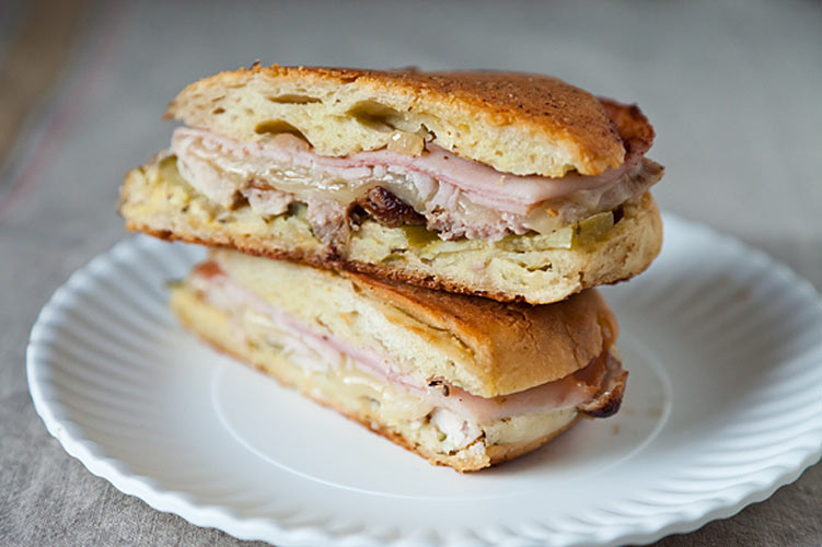 Cubano Mixto. Salty, tangy, gooey—this sandwich calls for being pressed like a panini, but it's even better grilled. Use a cast iron pan on your grill or hold it together with toothpicks, or risk losing some of that precious filling.