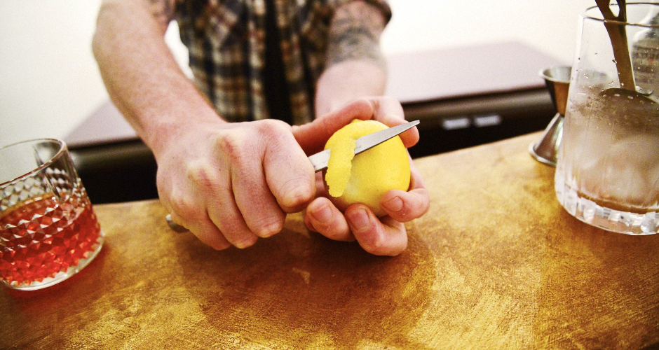 Now for the finishing touch: Zest a lemon peel. Take the knife and cut toward you, slowly, through the peel. (This is called a twist.)