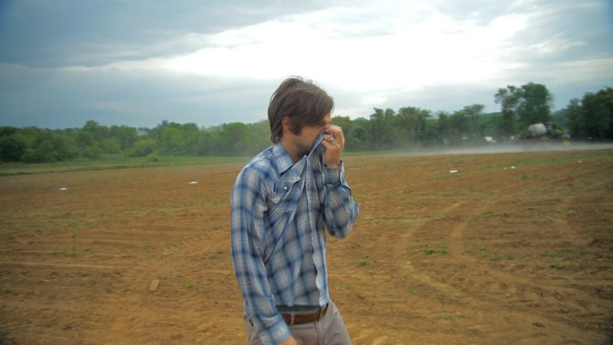 Filmmaker Jeremy Seifert covers his nose as a conventional farm is sprayed with pesticides. (Photo: