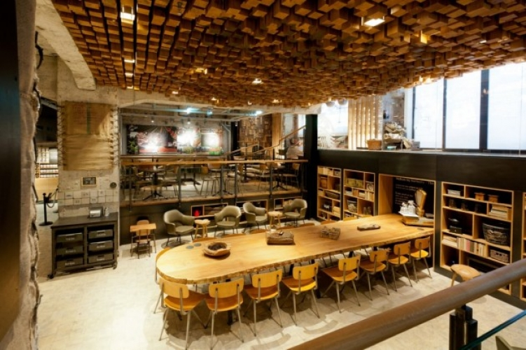 "This repurposed bank in Amsterdam is being pinned as a Starbucks ""laboratory,"" due to its mission of coffee experimentation and innovation. Should your eyes wander up, the ceiling features an undulating relief composed of 1,876 hand-cut and stained wooden blocks. (Photo:"