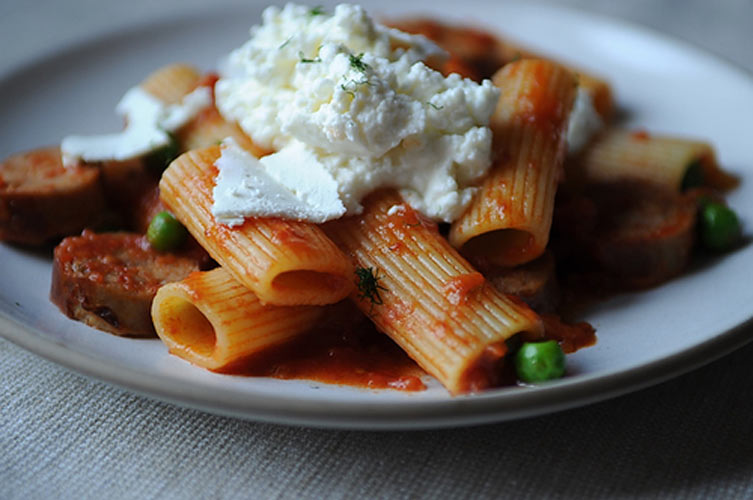 Rigatoni with Sausage, Peas and Fresh Ricotta.  A piquant tomato sauce laced with fennel and garlic gets an upgrade with savory pork and green peas. The creamy ricotta generously dolloped on top mellows the spice of the tomato sauce.