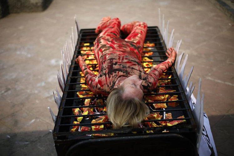 PETA co-founder Ingrid Newkirk lies down on a mock grill with fake flames during a protest against the consumption of meat in Mumbai, India, on November 6, 2013. (Photo: