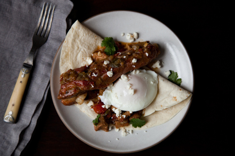 Huevos Rancheros Topped with Pork and Green Chile. Humble ingredients are transformed into a rich, comforting and deliciously satisfying dish. With a flavorful pork base, smoky chiles, bright cilantro, slightly tangy cheese, and a poached egg, this is hearty enough for dinner any night.