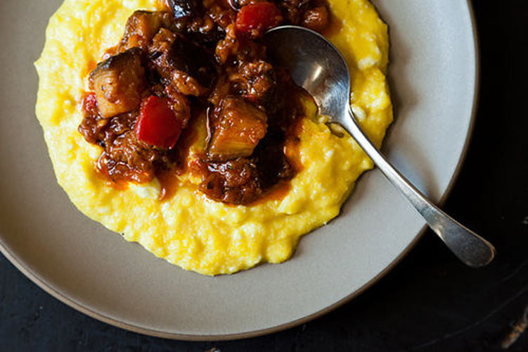 Yotam Ottolenghi's Sweet Corn Polenta with Eggplant Sauce. Fresh corn, cooked quickly, breaks down to a sweet soup in the food processor. Topped with a chunky, deep-flavored eggplant sauce, it is everything that you would want in a vegetarian dinner.