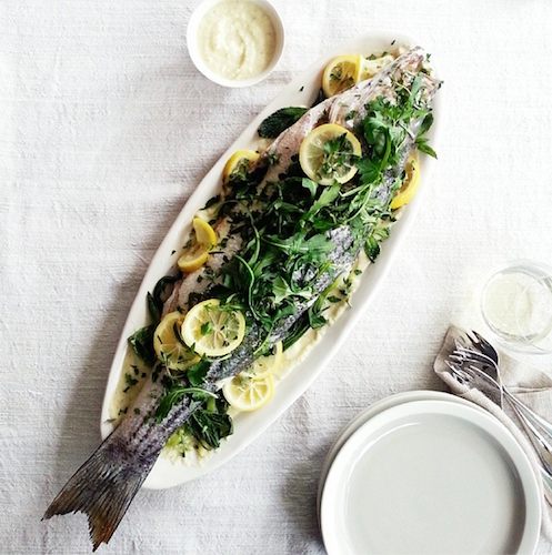 Whole roasted fish obscured by sliced lemons and arugula makes for a pretty picture. Photo: @helenedujardin