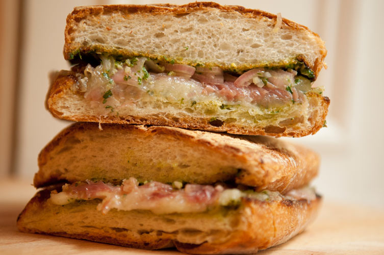 Prosciutto and Fontina Panini with Arugula Pesto. Garlicky, nutty arugula pesto and pickled shallots add depth and brightness to rich fontina and salty prosciutto.