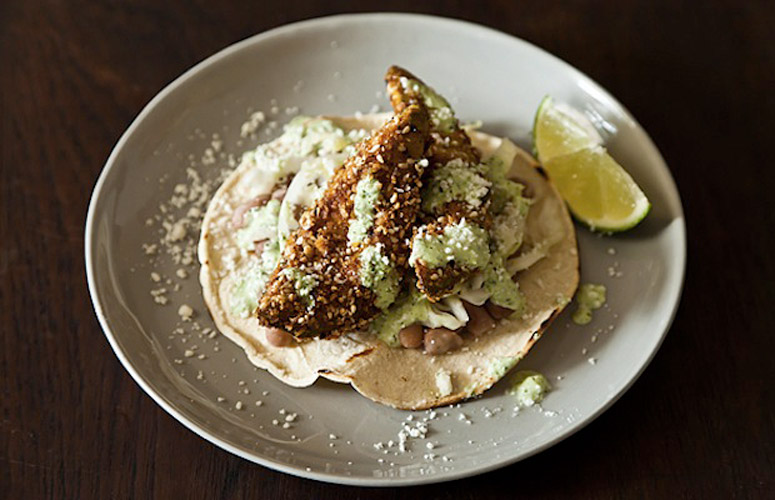 Fried Avocado Tacos with Sesame and Lime. Tacos like you've never seen: creamy, crispy breaded avocado stands center stage, supported by a sesame cabbage slaw, cilantro-kissed crema, and salt pork-simmered pinto beans.